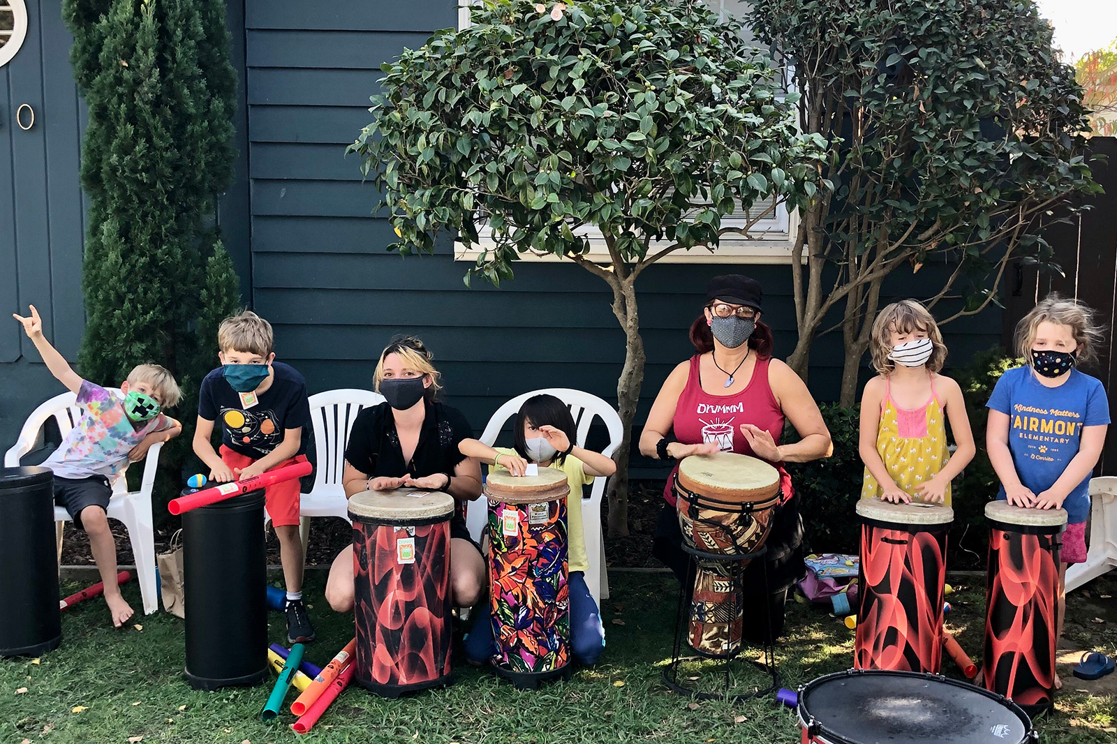 kids in chairs outside masks drums